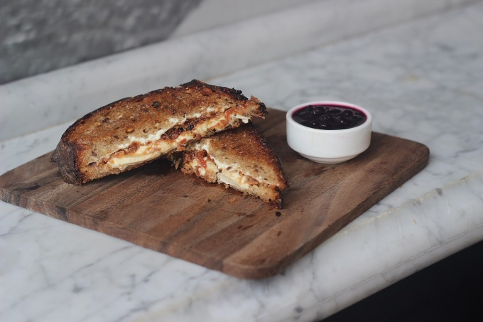 Grilled cheese sandwich with goat cheese, housemade bacon jam and blueberry compote