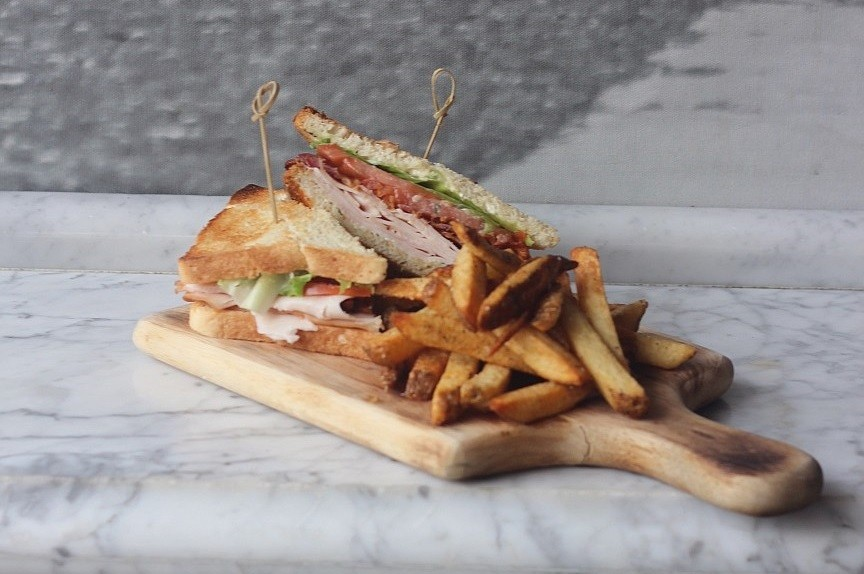 Turkey Club: Oven roasted turkey, beefsteak tomato, thyme aioli, applewood smoked bacon and lettuce served with hand cut fries